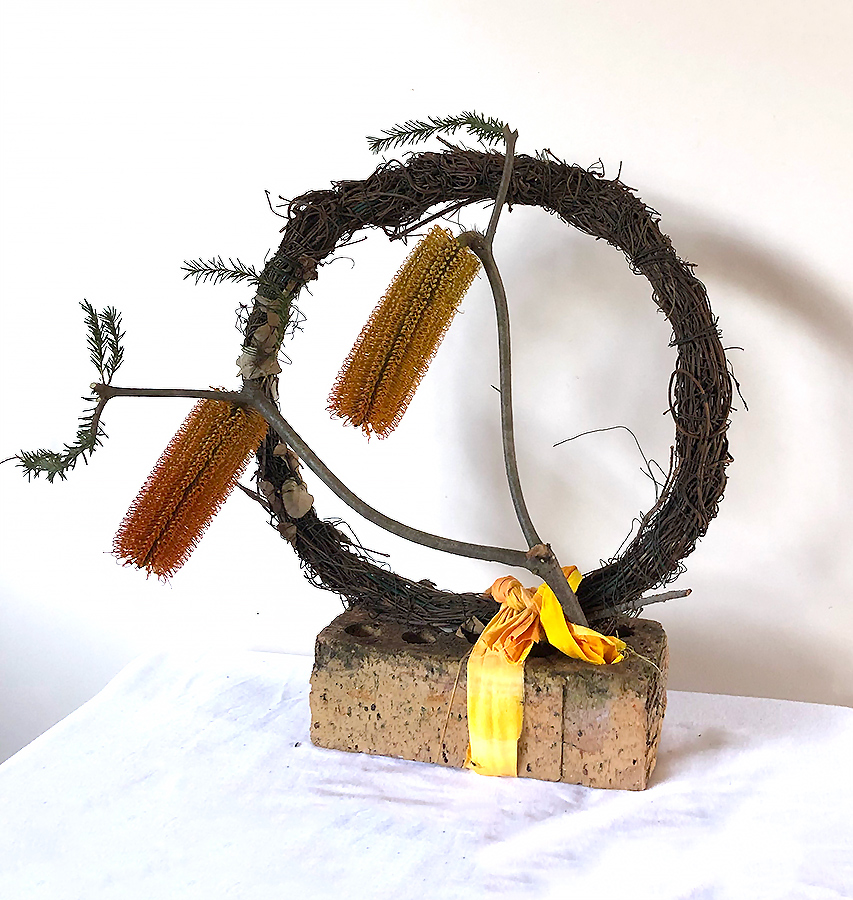 Merrilyn - Very ingenious to use the fabric to anchor the wine wreath and Banksia to a common house brick and all the time keeping the colours harmonious