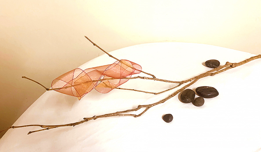 Shan - A very new student use a dried  branch with a chiffon ribbon joined and twisted onto the branch. She used a few pebbles to give weight to the work